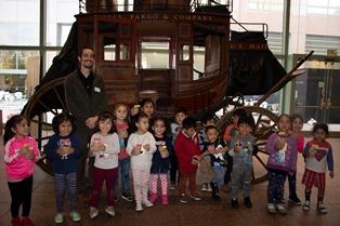 Trent Sneed, Wells Fargo Museum Curator, joins Hope Street children in front of an original Wells Fargo stagecoach.