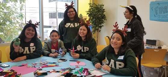 Five ladies from Phi Lambda UCLA make holiday cards with a young Hope Street boy