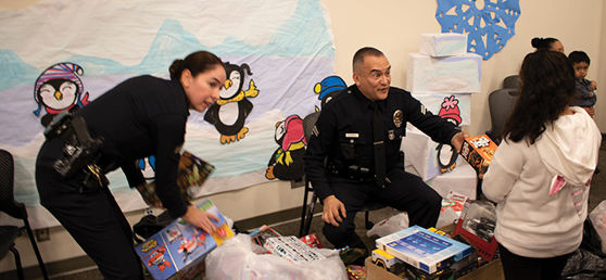 Two LAPD officers pass out gifts to young kids