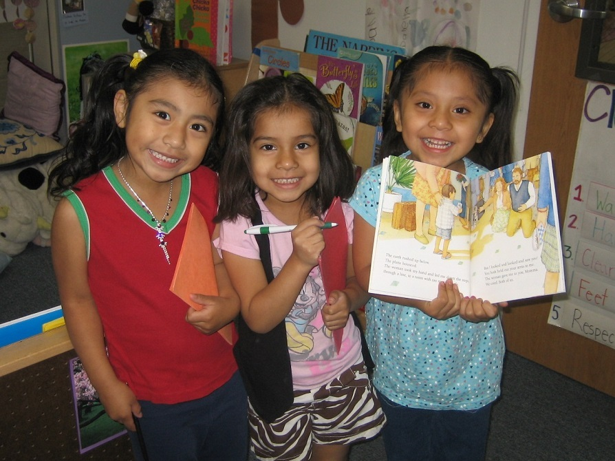 Three little girls smile while holding a picture book